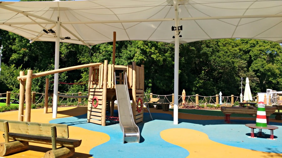 Shaded outdoor playground at Whitecliff Bay